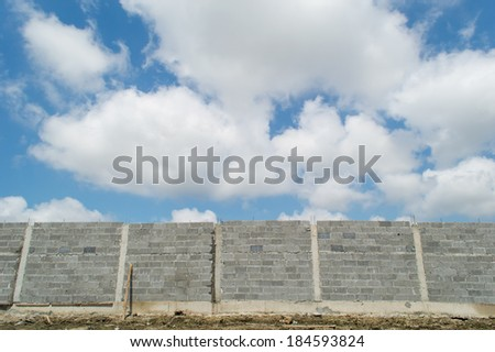 brick wall under construction with blue sky and cloud