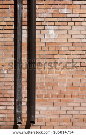 brick wall with a drain pipe - stock photo