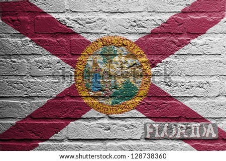 Brick wall with a painting of a flag isolated, Florida - stock photo