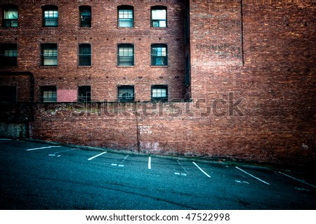 Brick wall with empty parking spots - stock photo