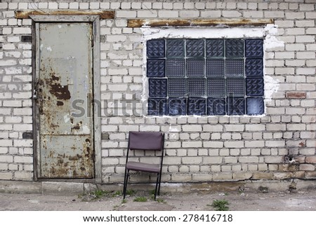 Brick wall with glass bricks window, rusted doors, old chair .
