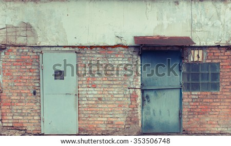 Brick wall with metal doors. Cold light. Vintage effect.