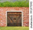 Brick wall with wooden door and trees - stock photo