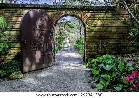 brick walled English garden arch gate that opens to a tree lined path in an english garden that goes on forever - stock photo