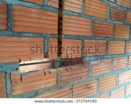 brick walls cracked before electric sockets installationat house construction site  - stock photo