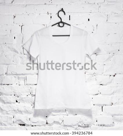 brick whitewashed wall with white shirt on hanger - stock photo