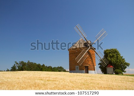 Brick windmill in a field of corn. Blue sky in the background. (Chvalkovice, Czech Republic) - stock photo
