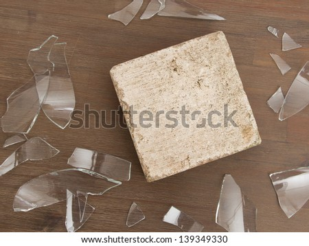 Brick with broken glass, violence concept, isolated on wood - stock photo