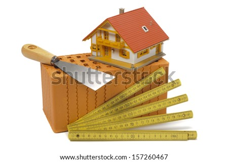 brick with tools for house building over white background