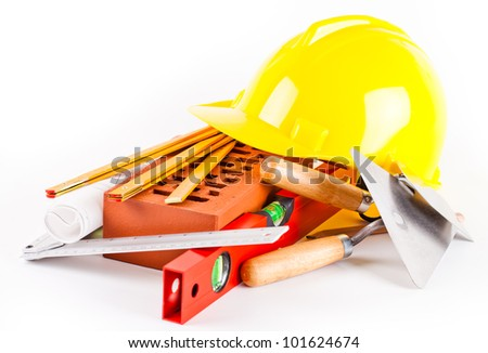 brick, yellow hard hat, tools and construction plans isolated on white background - stock photo