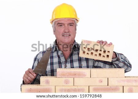 Bricklayer building wall - stock photo