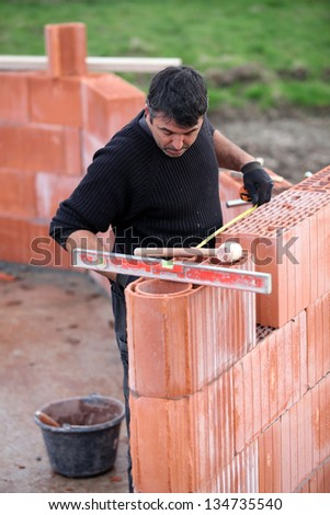 bricklayer erecting red brick wall - stock photo