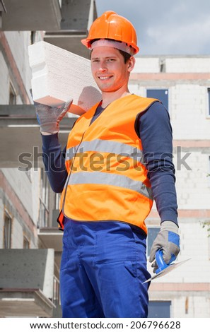 Bricklayer holding a brick at construction site - stock photo