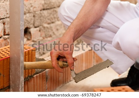 bricklayer laying bricks to make a wall, he is checking his work - stock photo