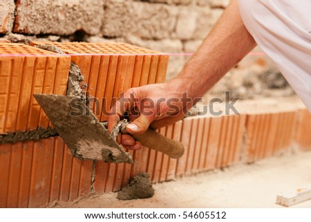 bricklayer laying, well, bricks to make a wall, he is pulling grout out of a joint with his trowel. This man is really working hard. - stock photo