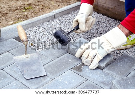 Bricklayer Places Concrete Paving Stone Blocks For Building Up A Patio,  Using Hammer And Spirit
