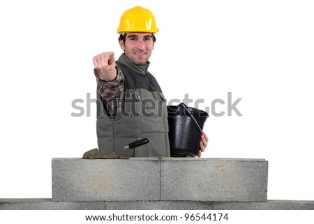 Bricklayer pointing ahead - stock photo