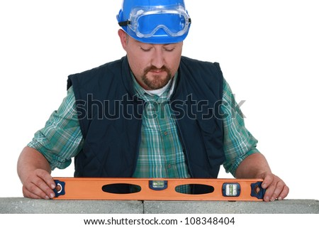 bricklayer taking measurements - stock photo