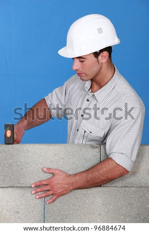 Bricklayer tapping down a block wall - stock photo