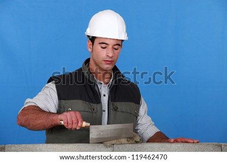 bricklayer using trowel - stock photo