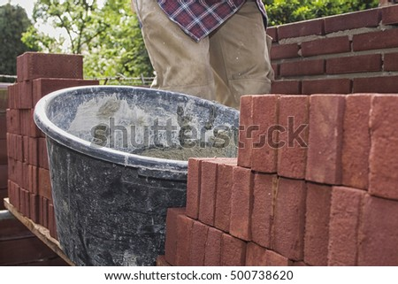 Bricklayer with a bucket full of homemade concrete