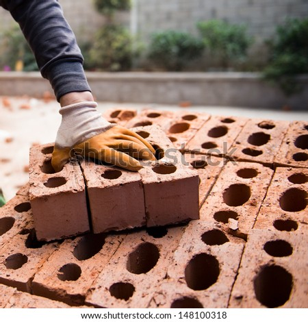 Bricklayer with brick at a construction site. - stock photo