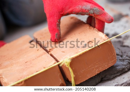 Bricklayer with brick at a construction site - stock photo