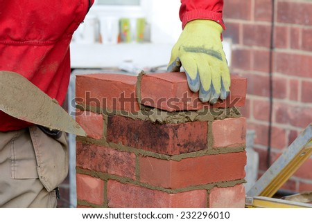 Bricklaying - laying brick to make a gate post - stock photo