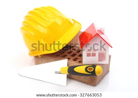 Bricks, trowel and helmet over white