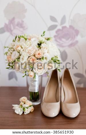 Bridal accessories: beige shoes and bride's bouquet - stock photo