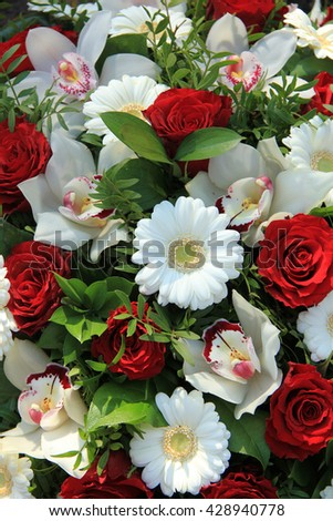 Bridal arrangement in red and white, cymbidium orchids, red roses and white gerberas