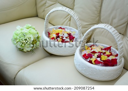 Bridal bouquet and baskets with rose petals for wedding ceremony - stock photo