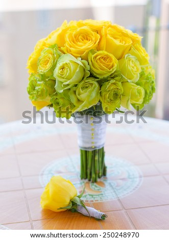 bridal bouquet and boutonniere of yellow, green and white roses arranged gradient on the table - stock photo