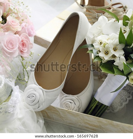 Bridal bouquet and bride shoes with roses.