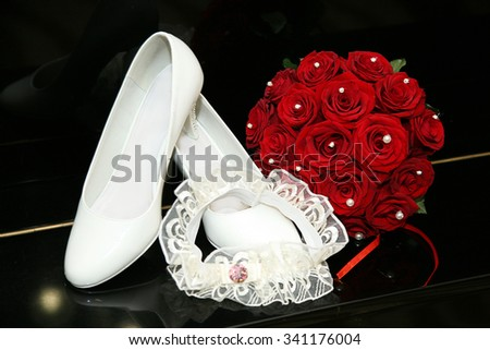 Bridal bouquet and shoes with the garter on a black background. Wedding bouquet of red roses closeup. - stock photo