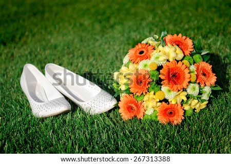 Bridal bouquet and white shoes bride lying on the grass. - stock photo