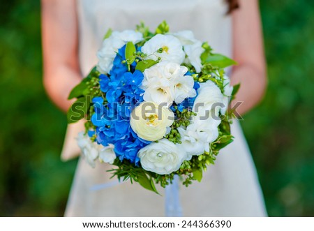 bridal bouquet blue with white flowers in the bride's hands. - stock photo
