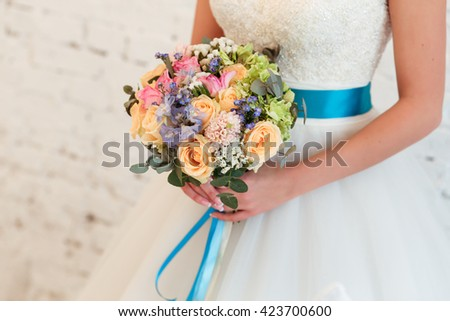 Bridal bouquet of flowers in a bride's hands - stock photo