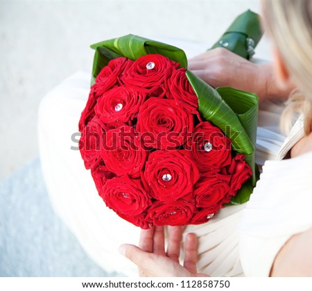 Bridal Bouquet of red roses with water droplets and crystal gems - stock photo