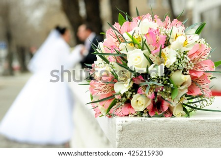 bridal bouquet of roses lying on the railing on the background of the bride and groom - stock photo