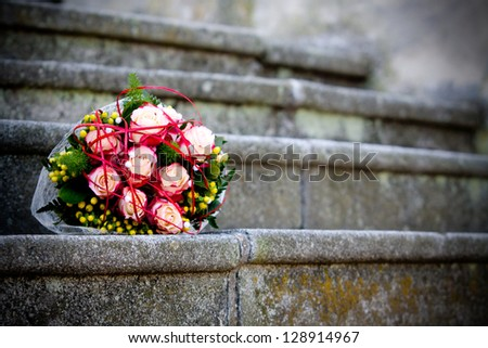 bridal bouquet of roses on the steps of the church