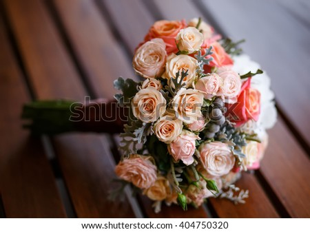 Bridal bouquet of various flowers on wooden table in cafe