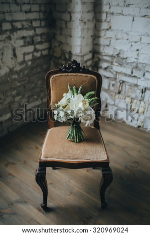 bridal bouquet of white flowers and greenery is on a vintage chair against a white brick wall in loft - stock photo