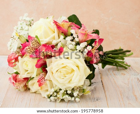 Bridal bouquet of white flowers on wooden surface. Summer wedding day, unusual designer florist bouquet of delicate roses. Wedding rings. Free space for text.  - stock photo