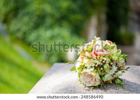Bridal bouquet on a granite column, Wedding bouquet - stock photo
