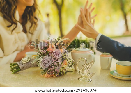 bridal bouquet on the table in the background of bride and groom holding hands - stock photo