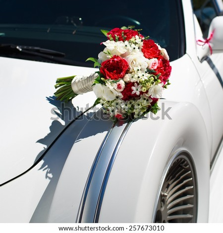 Bridal bouquet on wedding limo. - stock photo