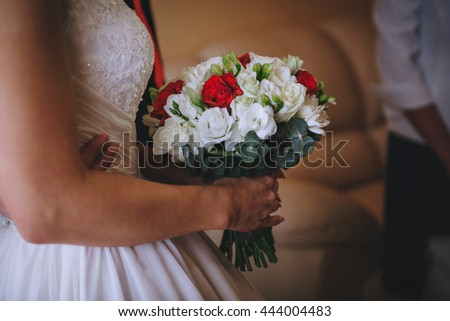 Bridal bouquet red white flowers in hands of bride.
