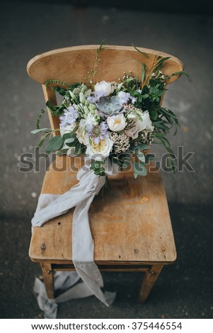 Bridal bouquet. The bride's bouquet. Beautiful bouquet of white, blue, pink flowers and greenery, decorated with long silk ribbon, lies on vintage wooden chair - stock photo
