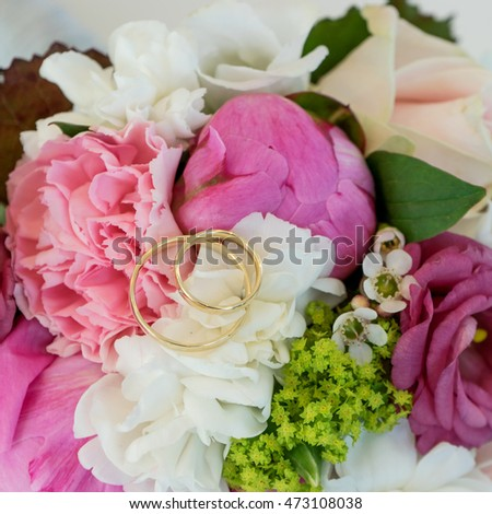 Bridal bouquet with pink and white flowers and golden wedding rings / bridal bouquet / wedding